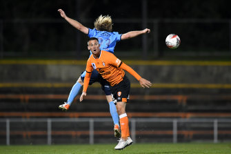 Brisbane Roar's Jordan Courtney-Perkins  competes for the ball with Rhyan Grant of Sydney FC.