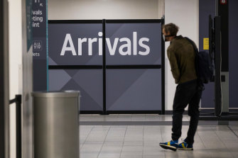 A traveller, wearing a protective face mask, passes through the arrivals area after landing at London Luton Airport on Friday.