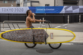 A surfer cycles past an Olympic banner in Fujisawa in June.