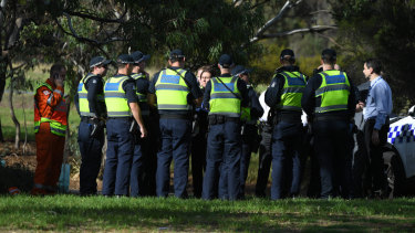 Uniformed police, detectives and members of the State Emergency Service at the scene in Parkville where a woman's body was found on Saturday morning.