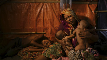 Rohingya woman Fatima Begum comforts her twins Asia and Rubina as her sick son Sadeka lays by her side at the Balukhali camp in Bangladesh. Some 900,000 Rohingya fled Myanmar for Bangladesh two years ago.