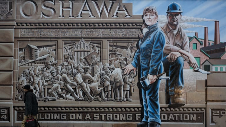 A pedestrian walks past a mural depicting workers in Oshawa, Ontario, Canada. After churning out cars and trucks forGeneral Motors for more than a century, the town could find itself without a car plant.