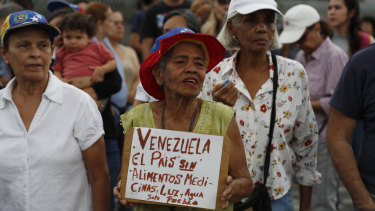 """A woman holds a sign that reads in Spanish: """"Venezuela, a country without food, medicine, light, and water. Only people."""""""