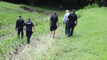 Police search the scene where two bodies were found in a drain running behind the Aitkenvale Library in Townsville.
