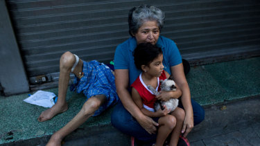 A woman holds a child outside in Caracas, following the earthquake.