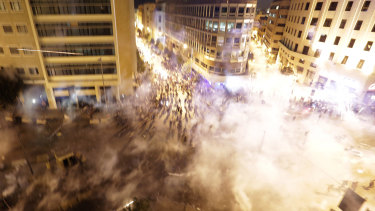 Lebanese riot police fire tear gas during a protest against government's plans to impose new taxes in Beirut, Lebanon.