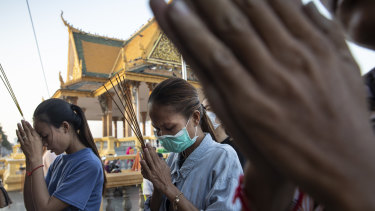 Cambodian women pray at a Buddhist shrine. Cambodia's tourism and real estate sectors could experience slowdowns due to the COVID-19.