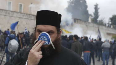 A monk protects himself from tear gas during clashes  in Athens on Sunday.