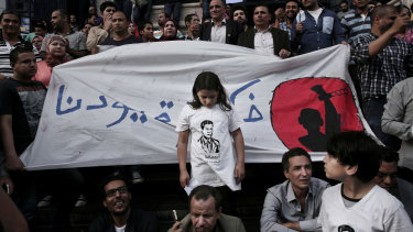 """A 2016 protest to mark World Press Freedom Day in Cairo, where a girl stands in front of a banner reading """"Remove our shackles""""."""