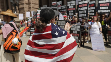 """Ignoring social distancing and mandates to wear masks for other face coverings, protesters attend an """"Open Texas"""" rally at the Texas State Capitol on Saturday."""