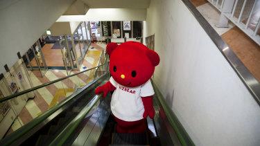 Bizbear, a mascot, rides the escalator at the factory of Kigurumi.biz, a mascot-maker based in Miyazaki, Japan in 2015.