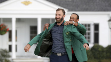 Dustin Johnson is presented the green jacket by Tiger Woods.