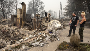 Derek Trenton and Shawna Haptonstall  look at the ruins of Derek's parents home in Talent, Oregon as wildfires devastate the region.