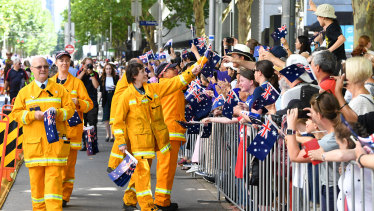 CFA volunteers are greeted by the crowd watching the parade.