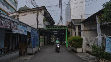 A motorcycle delivery driver walks the empty street of a neighborhood in Jakarta, Indonesia.