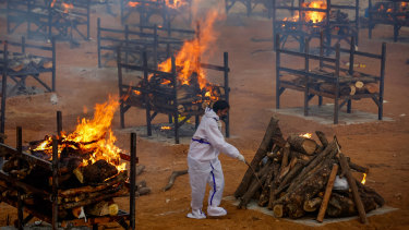 A man performs the last rites for a COVID-19 victim at a temporary crematorium in Bengaluru, India.