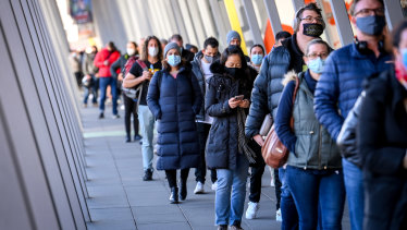 People queue up for COVID-19 vaccination at the Melbourne Convention and Exhibition Centre early on Wednesday morning.
