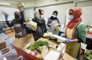Afshan Mantoo (centre) and her group of volunteers preparing food at their kitchen in Coburg.