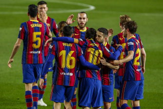 Lionel Messi is congratulated by Barcelona teammates after scoring against Getafe on Thursday (Friday AEST).