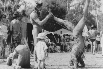 Mud-covered men do yoga at Down to Earth Confest in Wangaratta in 1984.