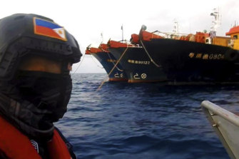 Members of the Philippine Coast Guard patrol beside Chinese vessels moored at Whitsun Reef, South China Sea, in April.