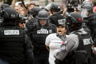 Police officers detain a protester against right-wing demonstrators in Portland.