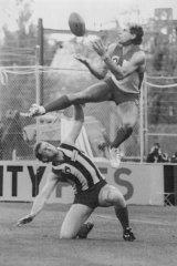 Studs up?: Warwick Capper flies over Mick Martyn.