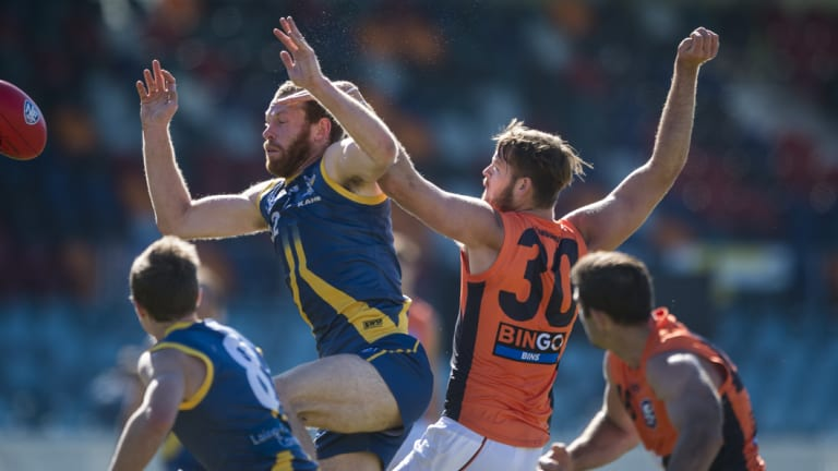Canberra's Cameron Milne and Giants' Matthew Flynn clash at Manuka Oval on Saturday.