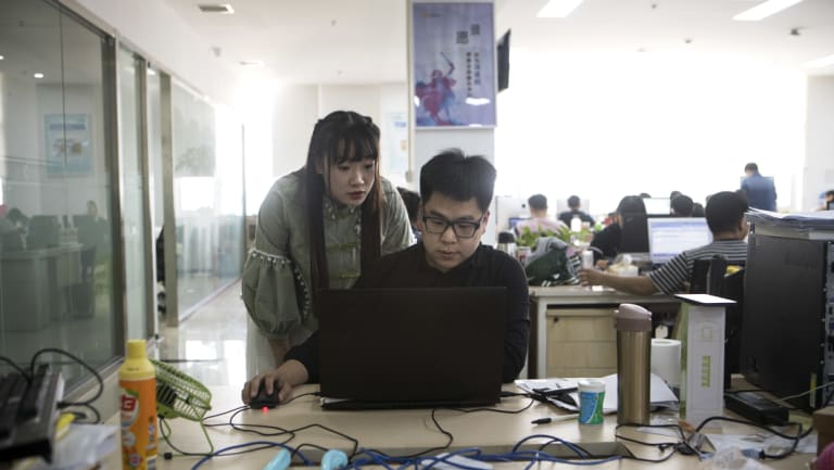 Shen Yue looks over the shoulder of one of her colleagues at the office.