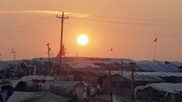 Rohingya Muslim refugees make their way between tents as the sun sets in Kutupalong refugee camp in Bangladesh.