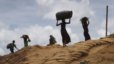Rohingya girls carry firewood on their heads as they make their way through Kutupalong refugee camp.