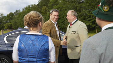 Markus Söder, second from left, the premier of Bavaria, arrives at a festival in Baierbrunn, near Munich, in June.
