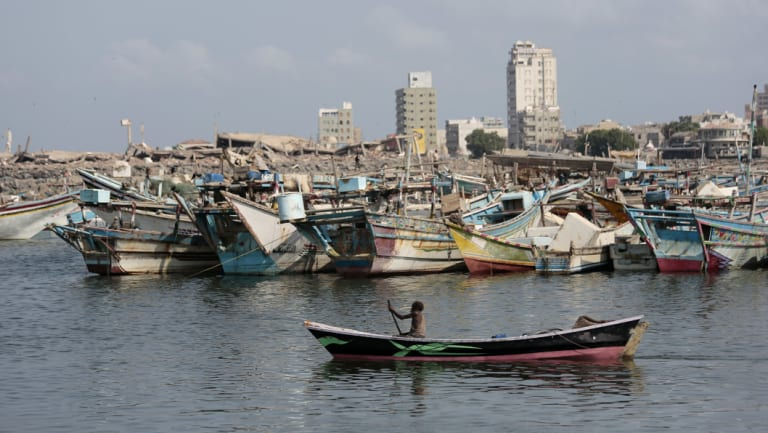 A fisherman paddles his boat past destroyed buildings on the coast of the port city of Hodeida, Yemen.