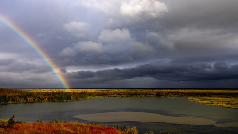 A rainbow shines over Esieh Lake, with the seep field of methane gas visible in the centre.