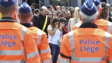 Women cry as they stand next to police officers for a moment of silence on Wednesday for shooting victims near the City Hall in Liege, Belgium.