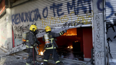 Firefighters force open the bottom floor of a small shopping centre that caught fire amid anti-government protests. The cause of the fire started is unconfirmed.