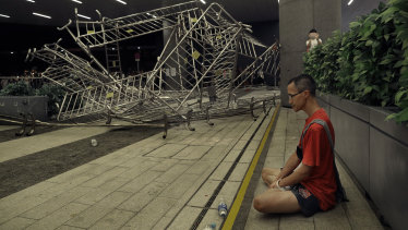 A protester sits near barriers after clashes during the rally against Hong Kong's extradition law.