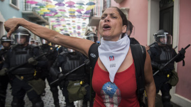 A woman gives a thumbs down as protesters approach La Fortaleza governor's residence on Sunday.