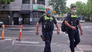 Police stand guard at the entrance of the Holiday Inn in Melbourne on Tuesday.