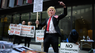 A man wears a Donald Trump mask as supporters of the Wikileaks founder Julian Assange gather outside the Old Bailey on September 14.