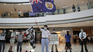 Protesters wave a Hong Kong colonial flag in a shopping mall during a protest against China's national security legislation for the city, in Hong Kong in May.