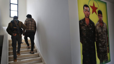 A Kurdish prison security guard, left, escorts a 19-year-old former IS fighter, into the courtroom.
