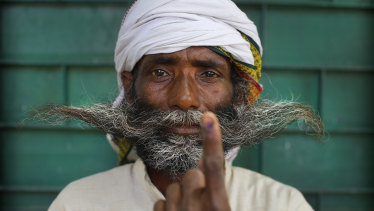 An Indian displays indelible ink mark on his index finger after casting his vote on the outskirts of Varanasi, India.