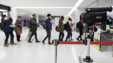 Passengers walk past a thermal scanner upon their arrival at Narita airport in Japan.