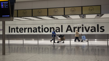 Arriving passengers walk past a sign in the arrivals area at Heathrow Airport in London.