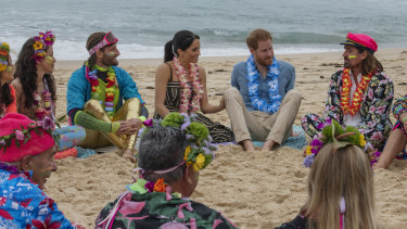 Prince Harry and Meghan Markle join One Wave's 'anti bad vibes circle' at Bondi Beach in October last year.