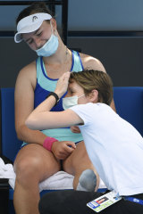 Barbora Krejcikova of the Czech Republic is treated by a trainer during an Australian Open lead-up match.