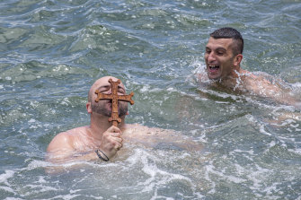 'I caught the cross first': Mikes Legkos (left) grabbed the cross before the official pack at the Greek Orthodox Blessing of the Waters swim at Princes Pier.