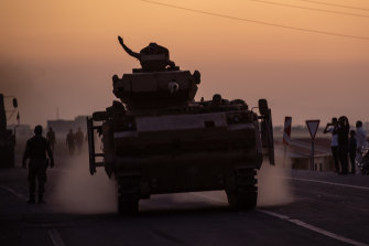 People wave as Turkish soldiers prepare to cross the border into Syria at Akcakale, Turkey.