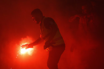 A supporter marshal grabs a flare lit by Wanderers fans during last week's derby.